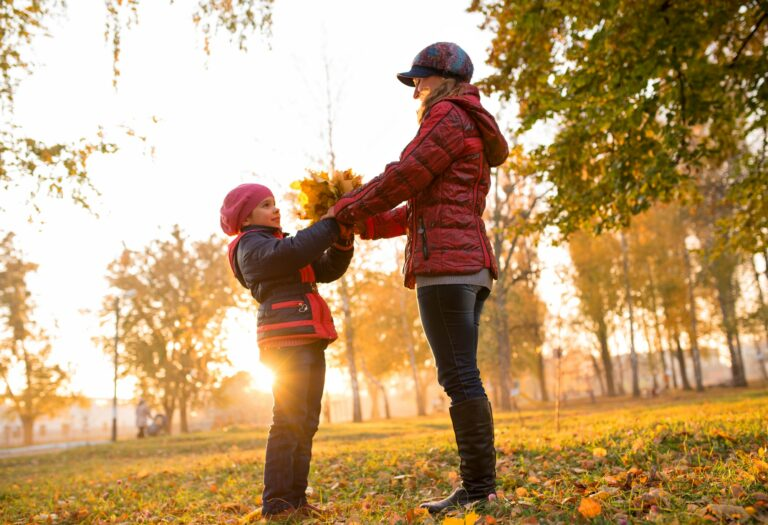 Charming young mother and daughter in a warm autumn park